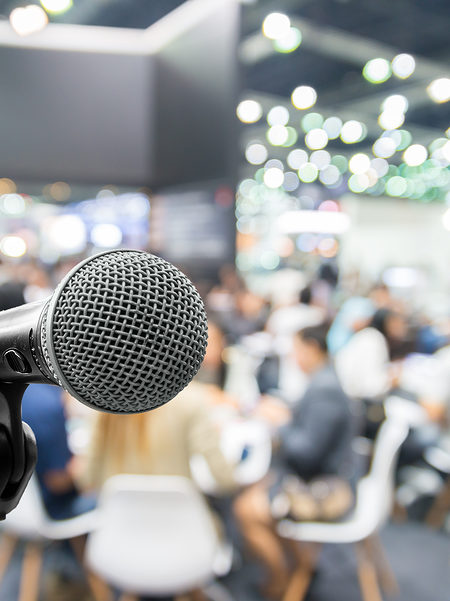 Microphone with abstract blurred photo of conference hall or seminar room with attendee and bokeh Business meeting concept
